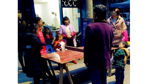 家长孩子围着一张自制简陋球桌打乒乓球,温馨!